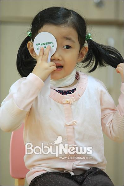 베이비뉴스 이기태 기자 = '비행기... 나비에요!' 10월 13일 세계 눈의 날을 이틀 앞둔 11일 오전 한국실명예방재단이 진행하는 '초롱이 눈건강교실'이 서울 송파구 거여2동 거암어린이집에서 열리고 있는 가운데, 한 아이가 머리카락을 만지작거리며 시력검사를 하고 있다. likitae@ibabynews.com ⓒ베이비뉴스