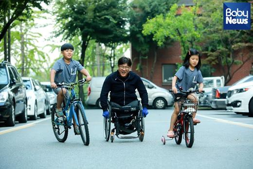 지난 9월 25일 인천시 연수구 한 아파트에서 휠체어를 탄 박대운(46) 씨와 자전거 탄 두 아이가 함께 놀이터로 향하고 있다. 최대성 기자 ⓒ베이비뉴스