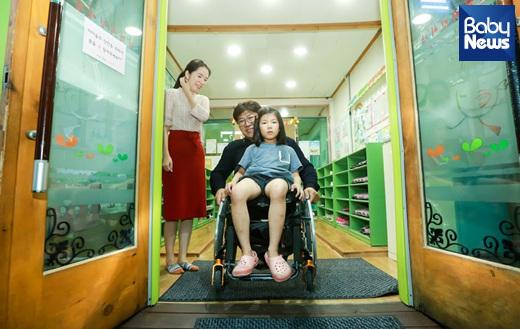 박대운 씨는 퇴근 후 집 근처 딸아이가 다니는 어린이집에 데리러 갔다. 아빠를 보자 딸아이는 휠체어에 폴짝 올라앉아사진을 찍자 당황한 모습이다. 최대성 기자 ⓒ베이비뉴스